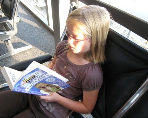 Child Reading at the Airport