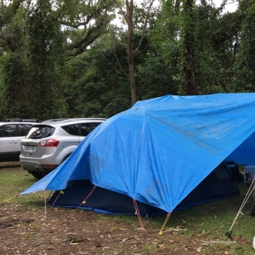 We erected our tent under the tarp. Using strong metal stakes and bungee cords I pulled the tarp out and away. & 8 Ways to Successfully Camp in the Rain | Travel Far Enough